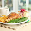 Roast chicken with french fries and cucumbers, cup of tea and dessert on  w — Stock Photo