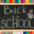 The words 'Back to School' written in chalk on the small school desk with v — Stock Photo #12713411