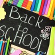 The words 'Back to School' written in chalk on the small school desk with v — Stock Photo #12713416