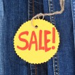 Many jeans with label Sale closeup — Stock Photo
