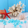 Decor of seashells on wooden table on blue wooden background - Stock Photo
