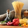 Pastspaghetti, vegetables and spices, on wooden table, on grey background — Stock Photo #12714644