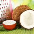 Coconuts wirh pink grater on green bamboo mat close-up — Stock Photo