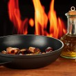 Roasted chestnuts in the pan and decanter with oil, salt and pepper on wood — Stock Photo #12714925