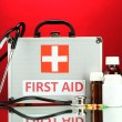 First aid box, on red background - Stock Photo