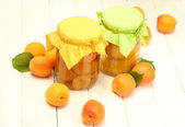 Canned apricots in a jars and ripe apricots on white wooden table — Stock Photo