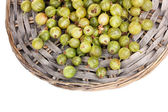 Green gooseberry on wicker mat isolated on white — Stock Photo