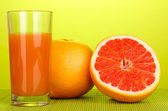 Grapefruit juice and grapefruit on bamboo mat on green background — Stock Photo