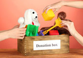 Donation box with children toys on red background close-up — Stock Photo