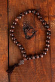 The Wooden rosary beads on wooden background close-up — Stock Photo