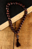 The Wooden rosary beads and holy bible on wooden background close-up — Stock Photo
