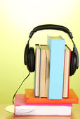 Headphones on books on wooden table on green background — Foto Stock