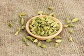 Cardamomo verde en un tazón de barro en primer plano de fondo de lona — Foto de Stock