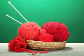 Red knittings yarns in basket on wooden table on green background — Stock Photo
