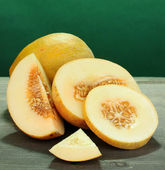 Cut ripe melons on wooden table on green background — Stock Photo