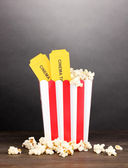 Popcorn with tickets on wooden table on grey background — Stock Photo