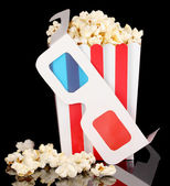 Popcorn and glasses isolated on black — Stock Photo