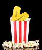 Popcorn with cinema tickets isolated on black — Stock Photo