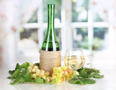 Bottle of wine with grape leaves of window background — Stock Photo