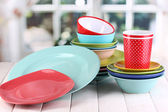 Colorful tableware on wooden table on window background — Stock Photo