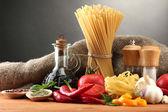 Makaron spaghetti, warzywa i przyprawy, na drewnianym stole, na szarym tle — Zdjęcie stockowe