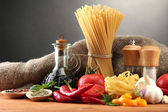 Pasta spaghetti, vegetables and spices, on wooden table, on grey background — Zdjęcie stockowe