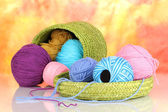 Colorful yarn for knitting in green basket on colorful background — Stock Photo
