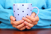 Hands holding mug of hot drink close-up — Stock Photo