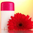 Deodorant with flower on red-yellow background - Stock Photo