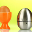 Egg timer and egg in orange stand on blue background — Stock Photo