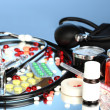 Medicines and a stethoscope on a blue background close-up - Stock Photo