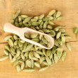 Green cardamom in wooden spoon on wooden background close-up - Stock Photo