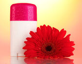 Deodorant with flower on red-yellow background — Stock Photo
