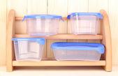 Kunststoffbehälter für lebensmittel auf regal auf hölzernen hintergrund — Stockfoto