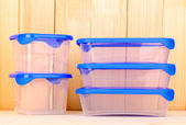 Plastic containers for food on wooden background — Stock Photo