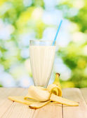 Banana milk shake on wooden table on bright background — Stock Photo