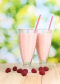 Raspberry milk shakes on wooden table on bright background — Stock Photo