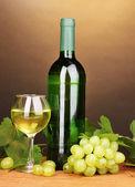 бутылка вина большой со стеклом на деревянный стол на коричневый фон — Стоковое фото