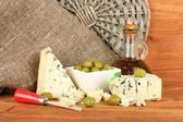 Composition of blue cheese and olives in a bowl on wooden background close- — Stock Photo