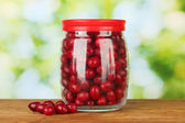 Fresh cornel berries in glass jar on green background close-up — Stock Photo