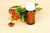 Botella de la medicina con las tabletas y las flores en la estera de bambú — Foto de Stock