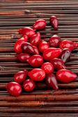 Fresh cornel berries on bamboo mat — Stock Photo