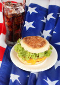 Tasty sandwich and glass with cola, on american flag — Stock Photo