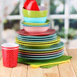 Colorful tableware on wooden table on window background - Stock Photo