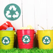 Recycling bins on green grass near wooden fence — Stock Photo #12765572