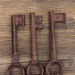 Three antique keys on wooden background - Stock Photo