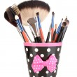 Makeup brushes in a black polka-dot cup isolated on white - Stock Photo