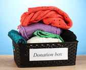 Donation box with clothing on blue background close-up — Stock Photo