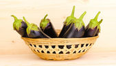 Fresh eggplants in basket on wooden background — Stock Photo