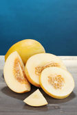 Cut ripe melons on wooden table on blue background — Stock Photo